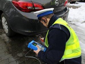 """policjant ruchu drogowego , która bada emisje spalin z """"wydechu""""  auta"""