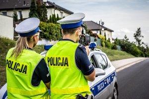 droga, umundurowani policjanci stoją obok radiowozu i kontrolują prędkość za pomocą laserowych mierników prędkości
