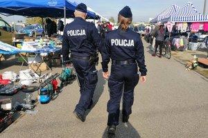 targowisko miejskie, umundurowani policjanci patrolują teren, w tle stragany handlowe