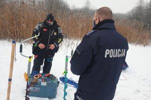 policjant z wędkarzem stoją na oblodzonym zbiorniku wodnym. w tle sprzęt poprawiający bezpieczeństwo na lodzie,