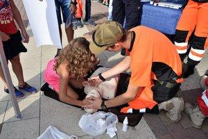 dziewczynka uczy sie pierwszej pomocy z ratownikami