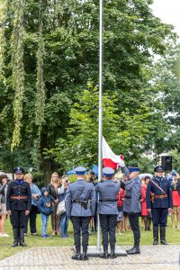 policjanci wraz z flagą państwową